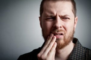 man with toothache helped by Denver Dentist
