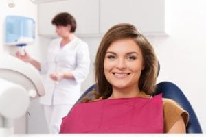 Young woman with beautiful white fillings visiting dentist