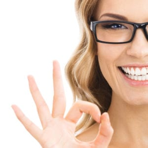 "blonde woman with beautiful smile giving the ""okay"" hand gesture in front of white background"