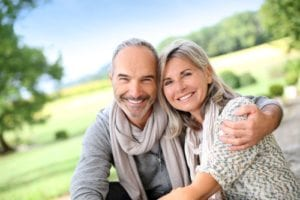 Outdoor portrait of middle aged man and woman smiling