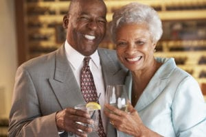 older African-American couple smiling and enjoying drinks at a bar