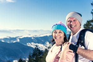 couple wearing beanies on top of a mountain smiling in front of a scenic mountain background