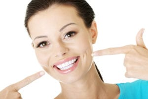 young woman pointing to her teeth and showing off her new smile makeover