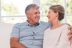 photograph of older couple smiling at each other in their home