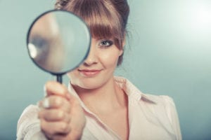 portrait of woman looking through a magnifying glass