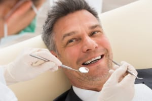 smiling man undergoing dental checkup
