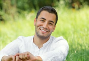 portrait of smiling young man sitting in grass outside