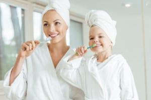 mom and daughter brushing teeth