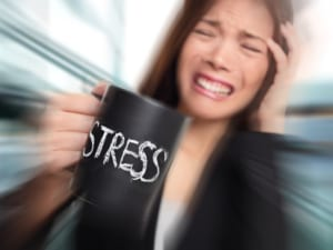 stressed woman holding coffee cup and clenching teeth