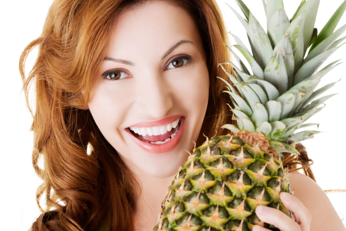 portrait of smiling red-headed woman with pineapple