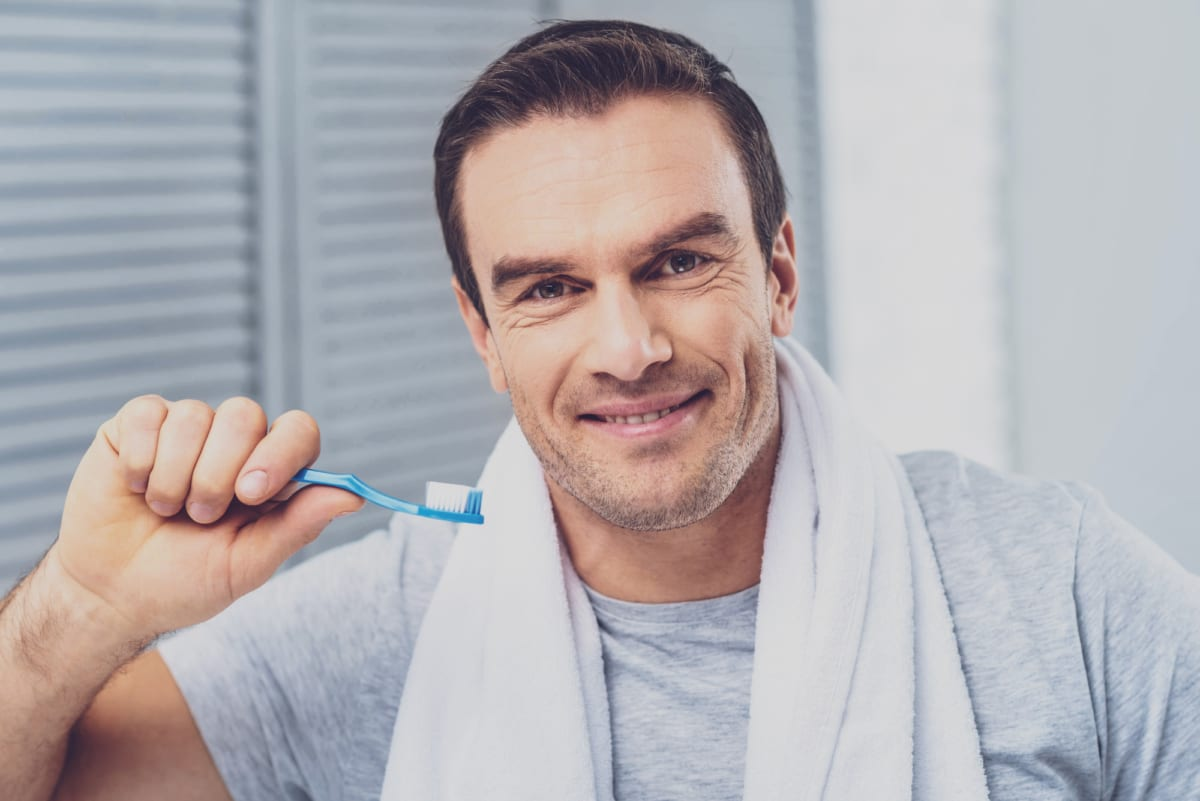 smiling middle-aged man brushing his teeth