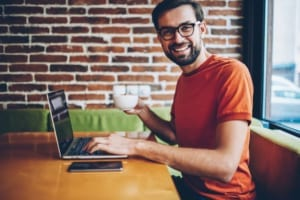 smiling young man in glasses drinking coffee and working on laptop