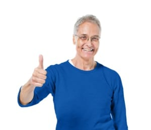 senior man in blue shirt smiling and giving thumbs up