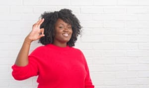 happy African-American woman in red shirt smiling and giving OK sign