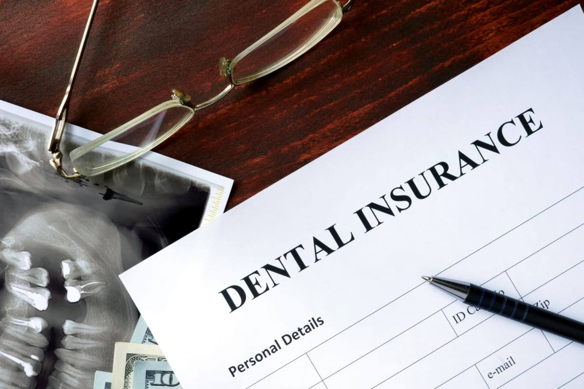 dental insurance papers with glasses on table