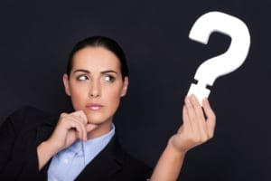 woman in business suit holding a question mark