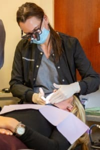 dental hygienist working on patient