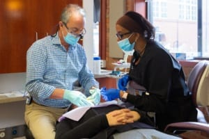 dentist and dental assistant operating on patient
