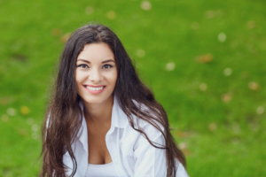 smiling young woman sitting on green grass outside