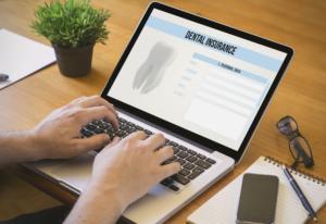 insurance dentist checking dental insurance on laptop