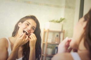woman flossing teeth in mirror