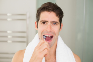 close up of man brushing teeth